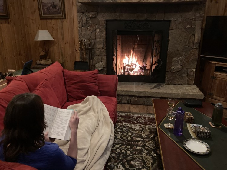 person reading under blanket on the couch by the fire in cabin in Colorado wilderness