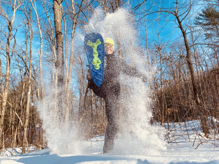 winter photo competition: person throwing snowshoe in the air with snow