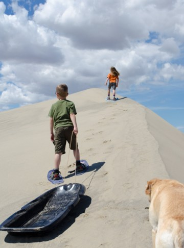kids walking up sand dune in snowshoes