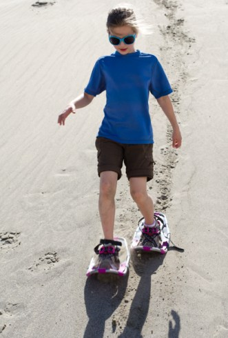 snowshoeing in summer: girl walking down a sand dune on snowshoes