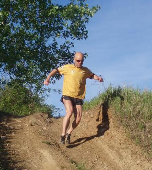 man running downhill on a trail