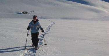 woman snowshoeing in New Zealand with poles with snow covered hills in background