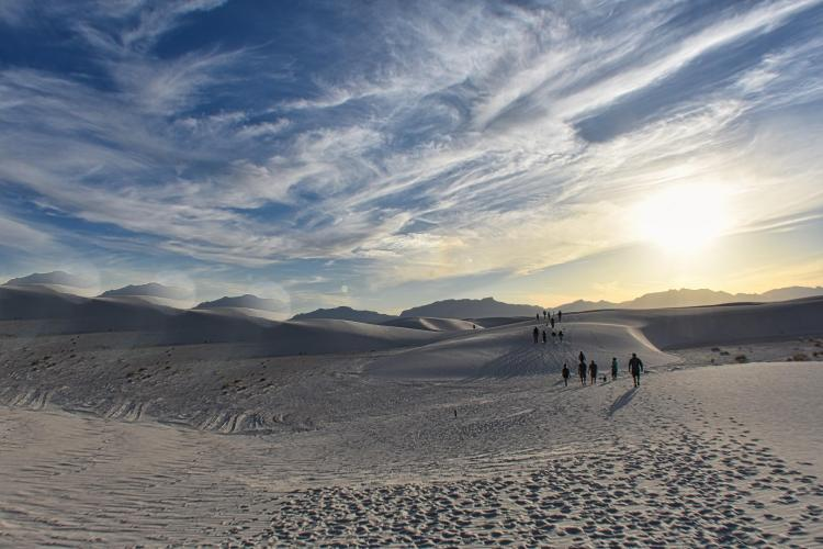 dunes with hikers in distance under clouds and sun