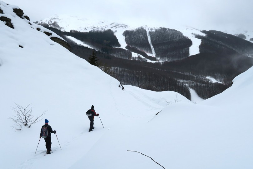 two snowshoers walking through hilly landscape