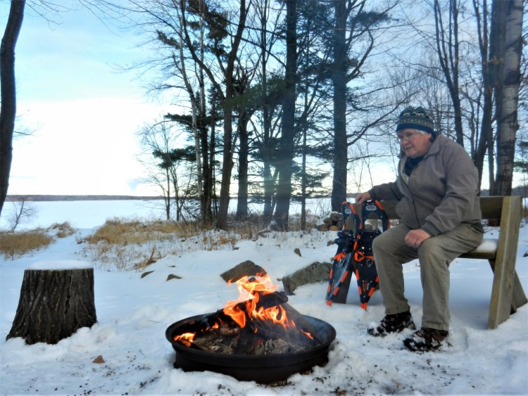 man with snowshoes near a winter campfire