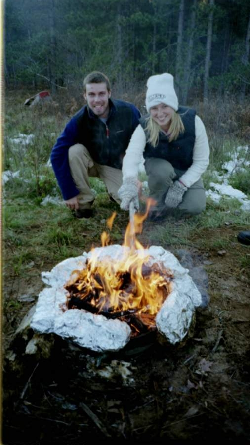 man and woman prepping food over campfire in winter
