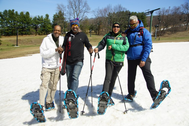 four snowshoers with snowshoes raised on snow at NBS snowshoe event