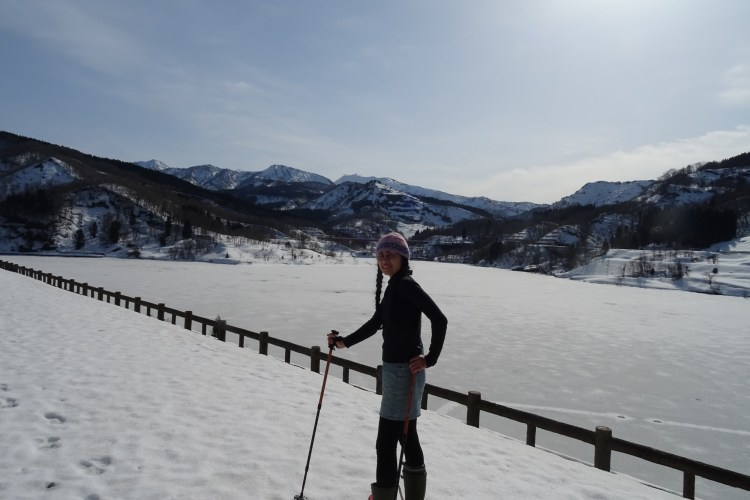 Sanjo, Niigata, Japan: person with snowshoes and poles on snowy route with mountains in background at Otani Dam