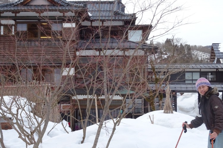 woman in front of inn with trees and snow in foreground