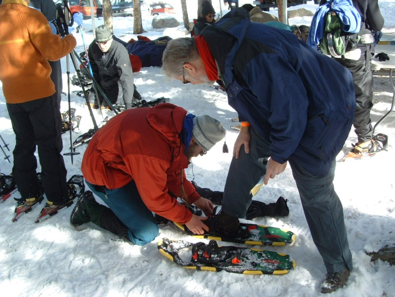 man helping another man put on his snowshoes