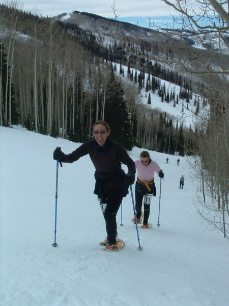 two women going up a hill on snowshoes and poles with racing numbers