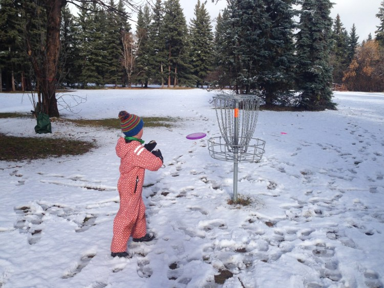 outdoor winter activities ideas: child playing disc golf in winter