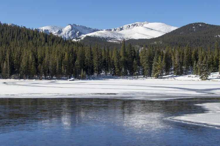 snowshoeing near denver co: echo lake with ice and mountains in trees in background