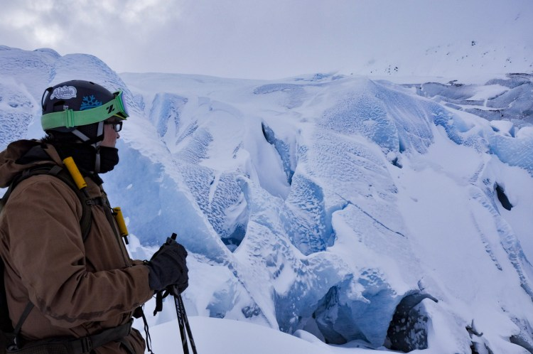 man inspecting snowy icebergs