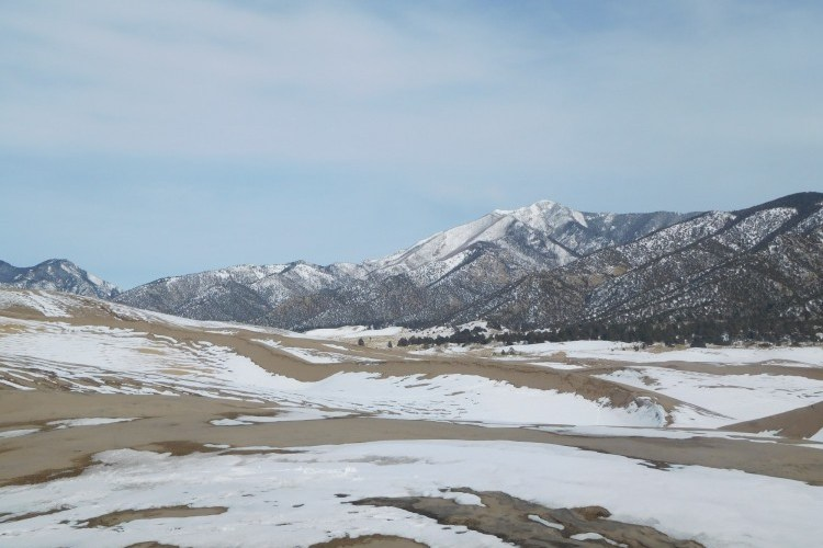 sand and snow at Great Dunes National Park with mountains in background