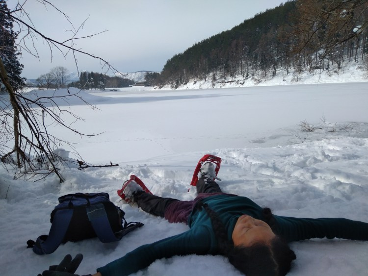 woman laying on back with snowshoes near a lake