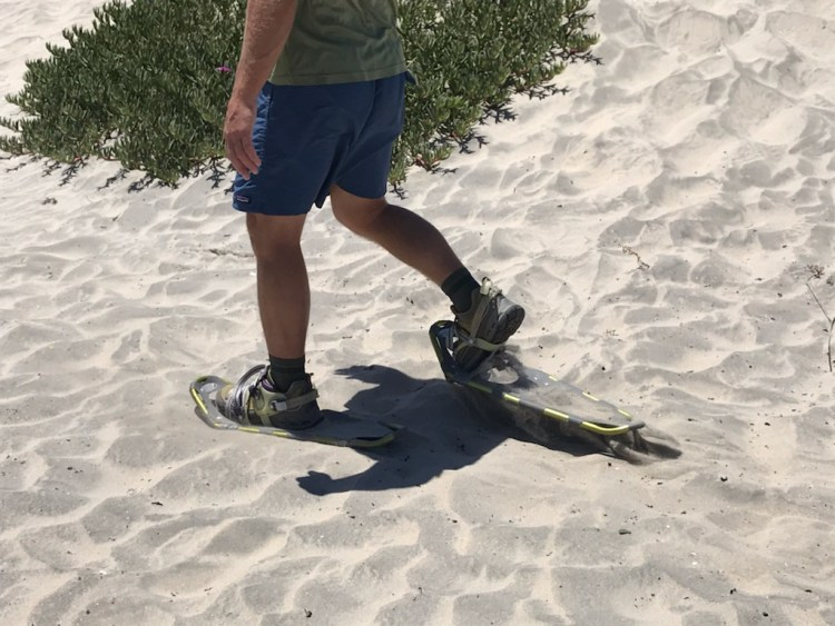 close up of snowshoes in sand while man is walking