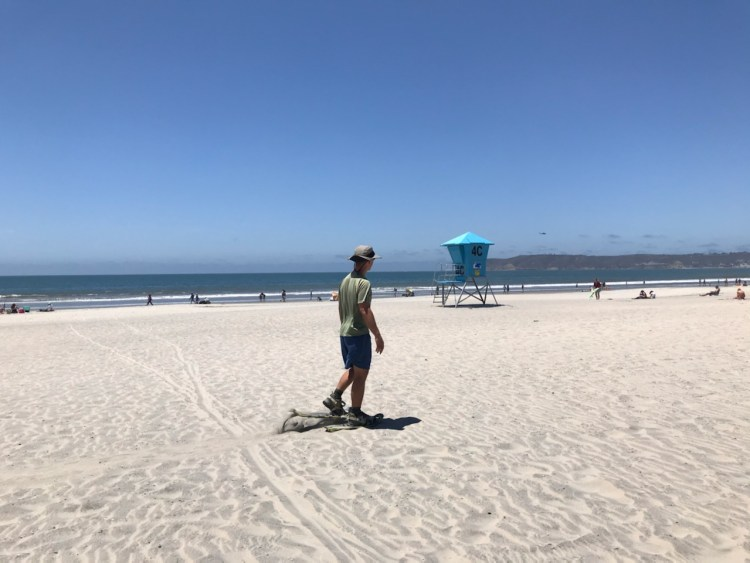man using snowshoes on a beach with tower in background