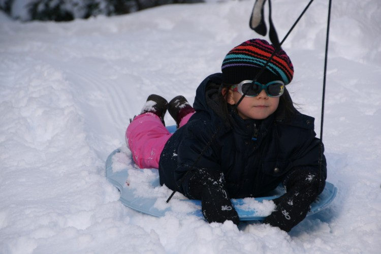 chld wearing sunglasses laying down on sled
