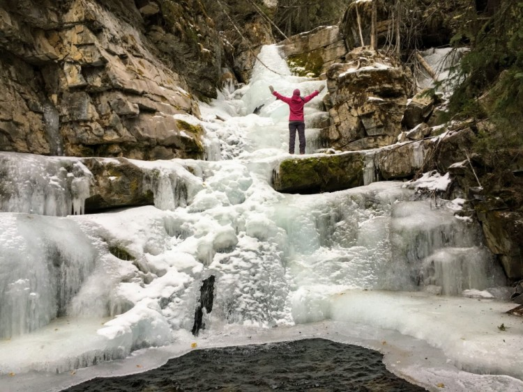 person standing with arms outstretched near top of Upper Falls, Kananaskis