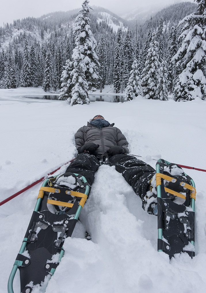 laying in snow on snowshoes