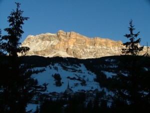 The first rays of the day's sun on Santa Croce Rock behind Badia