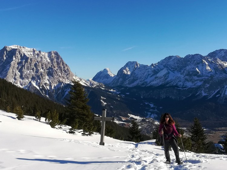 why hiking is good for you: snowshoer next to cross on mountain summit