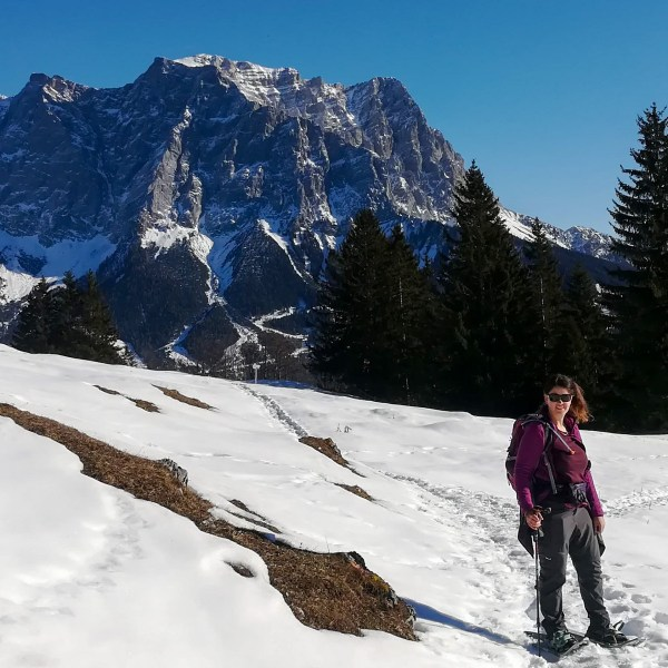 snowshoer facing camera with mountains (Alps) in the background