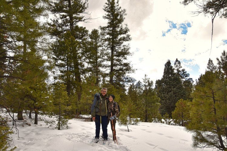 couple on snowshoes in front of trees under cloudy sky