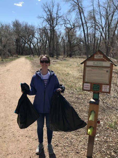 woman holding trash bags near natural area sign