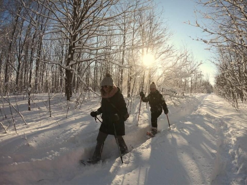 two women snowshoeing in deep snow with sun shining behind the trees
