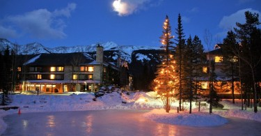 Pomeroy Lodge at night with frozen pond and Christmas lights