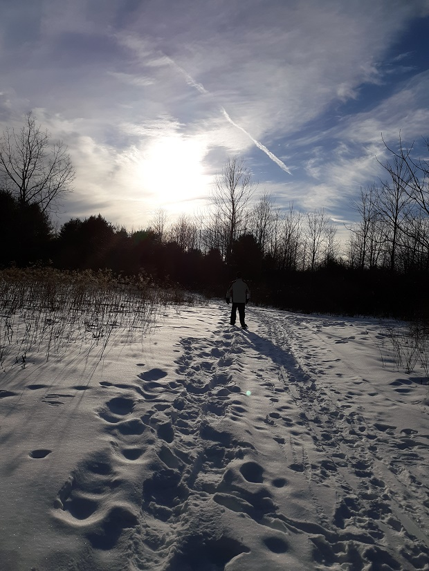 person snowshoeing in deep snow under sun and clouds