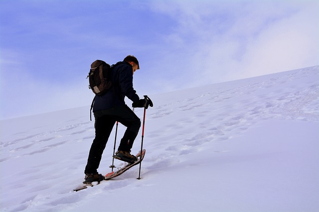 man ascending a hill in snowshoes