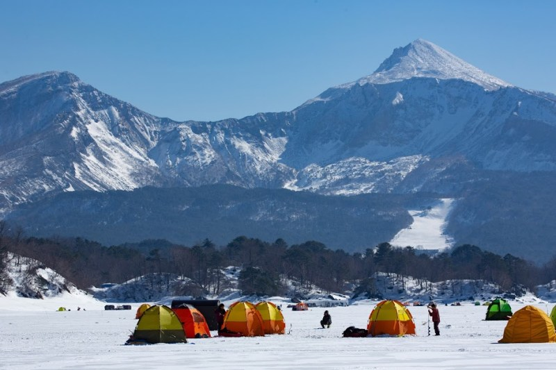 Urabandai winter activities: ice fishing tents on a frozen pond with mountains in the background