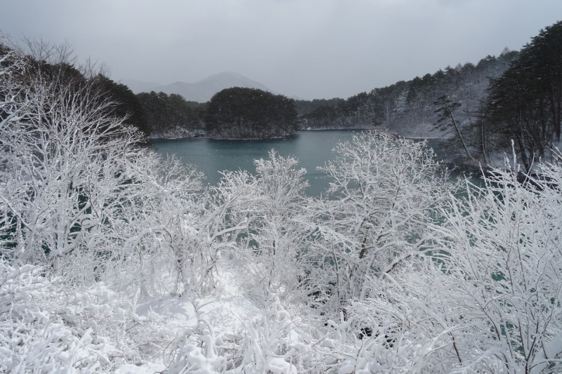 Urabandai lake in winter in with frosted over branches in front of it