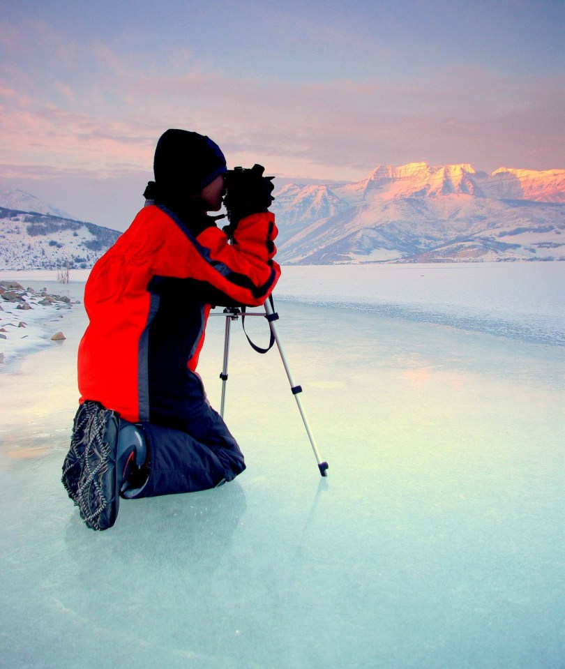person with camera on lake, wearing Yaktrax traction device