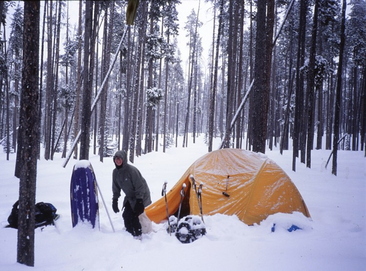 person at winter camp site in deep snow