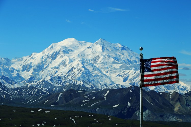 outdoor recreation veterans: US flag with snowy mountain in background