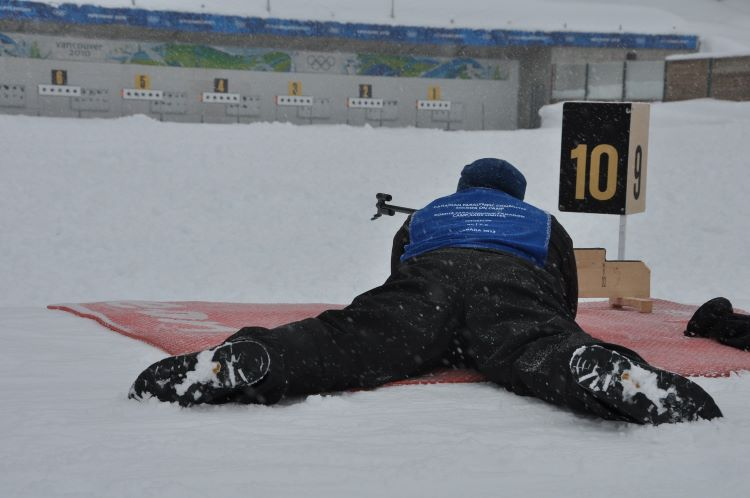 new sports to try: man in biathlon event shooting rifle