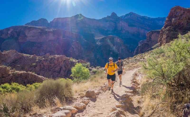 two men trail running with mountains in background