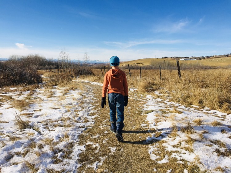 boy walking on trail partly covered by snow