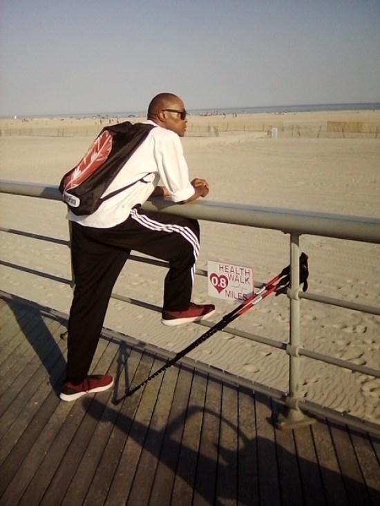 man on boardwalk looking at beach