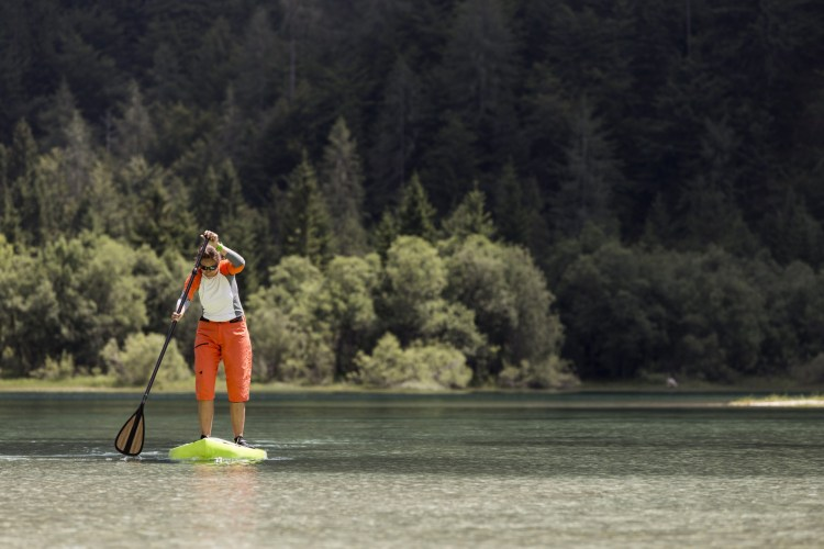 muscles used during paddleboarding: woman on a lake with trees in background