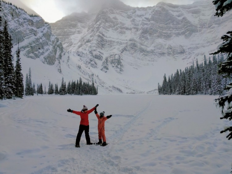 mother and son on snowshoes with arms outstretched at Rawson Lake, Kananaskis