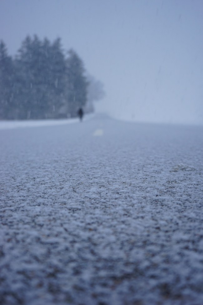 mental health winter: close up of snow on road with figure in background