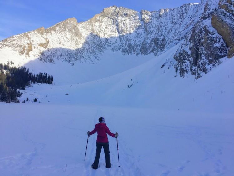 person on snowshoes and poles admiring view at Rummel Lake, Kananaskis