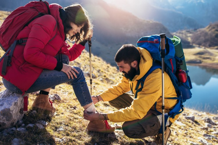 man helps woman to heal sprained ankle while hiking