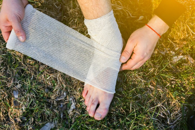 person wrapping sprained ankle while outdoors
