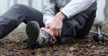 close up of person holding ankle on the trail